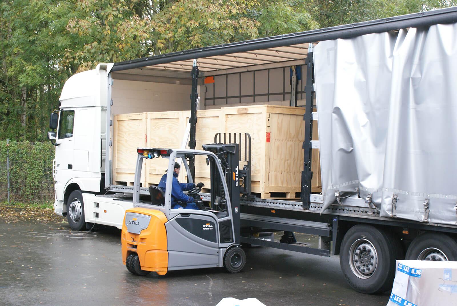 Kisten werden aus LKW geladen